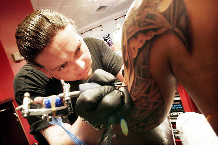 Tattoo artist Jack Omoto, who was raised in Waianae, works on a piece on